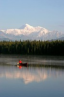 Man Canoeing on Byers lake with Denali in the background Southcentral Alaska Summer