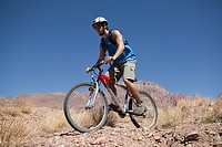 Man riding mountain bike in rocky terrain
