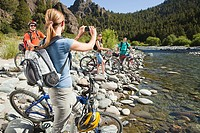Mountain bikers by a lake, woman taking photograph