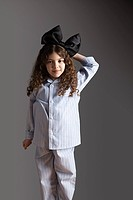 Young girl dressed in pyjamas with black hair bow