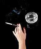 Female hand with cigarette in holder and ashtray