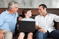 Three generations of males with laptop