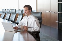 Business man in a meeting room using a laptop
