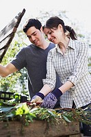 Young couple using compost bin