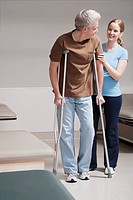 Physiotherapist assisting a patient in walking with crutches