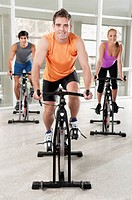 Three people working out on exercise bikes in a gym