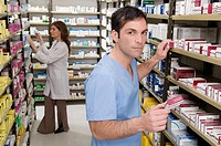 Male and a female pharmacist checking the medicines in the medical store