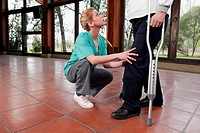 Physiotherapist assisting a woman in walking