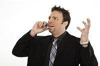 Caucasian businessman standing and talking on the cell phone and angry