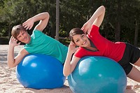 Couple exercising with fitness balls on the beach