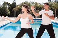 Couple exercising at the poolside