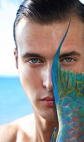 Hawaii, Oahu, Closeup creative Headshot of Male Model with a Colorful Parrot Fish next to his face