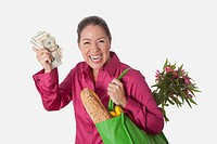 Woman holding a shopping bag of groceries and showing currency notes