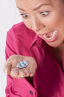 Woman looking at pills and shouting
