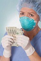 Female surgeon holding currency notes