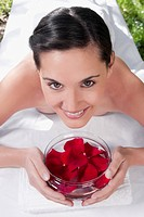 Portrait of a woman lying on a massage table holding a bowl of rose petals
