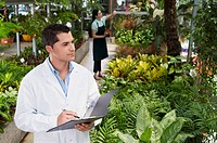 Scientist examining plants in a greenhouse