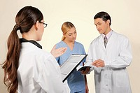 Doctors and a nurse discussing about medical record