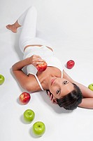 High angle view of a woman lying with red and green apples