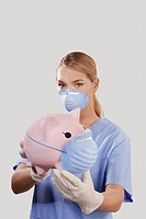 Female doctor wearing a flue mask and showing a piggy bank