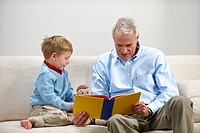 Young boy and grandfather reading book
