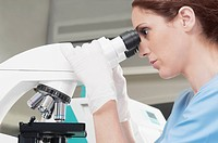 Female lab technician analyzing a sample through a microscope