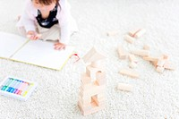 Baby girl drawing next to wooden building blocks