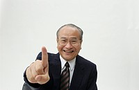 Portrait of Senior Man in Business Suit, Pointing at Camera