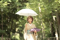 Portrait of mature woman in Kimono holding umbrella and gift, Kyoto city, Kyoto prefecture, Japan