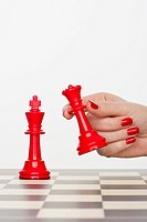 Hand holding red chess piece