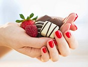 Hand holding chocolates a raspberry and a strawberry