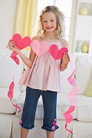 Young girl holding heart cut outs