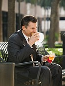 Businessman eating lunch on park bench