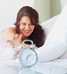 Woman reaching for alarm clock