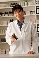 Pharmacist holding a bottle of prescription medication