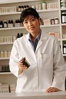Pharmacist holding a bottle of prescription medication