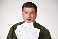 Man holding United States 1040 tax forms and feeling anxious about his taxes