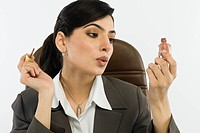 Businesswoman applying nail paint on fingernails in an office