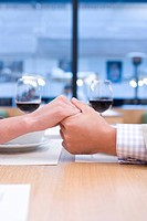 Close up of couple drinking wine and holding hands