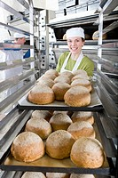 Baker putting pan of fresh loaves of bread in rack