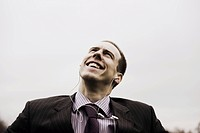Businessman with MP3 player looks up smiling
