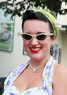 England, West Sussex, Goodwood Revival. Lady with red lipstick, hair net, and winged eyeglasses at Goodwood Revival.