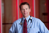 Doctor with stethoscope looking at camera red background