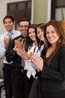 Business group portrait applauding and smiling indoors