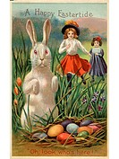 A vintage Easter postcard of two girls running towards a rabbit and a nest of colored eggs