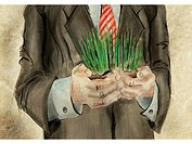 A businessman holding grass
