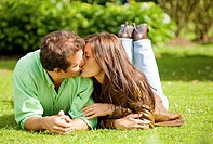 couple portrait kissing on the floor outdoors where both are looking happy