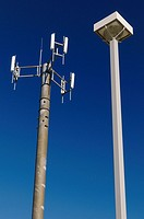 Cell phone communications tower against a blue sky with a lamp post