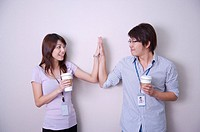 Young man and woman holding coffee together and making high_five