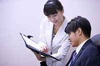 Young woman showing document folder to young man with smile